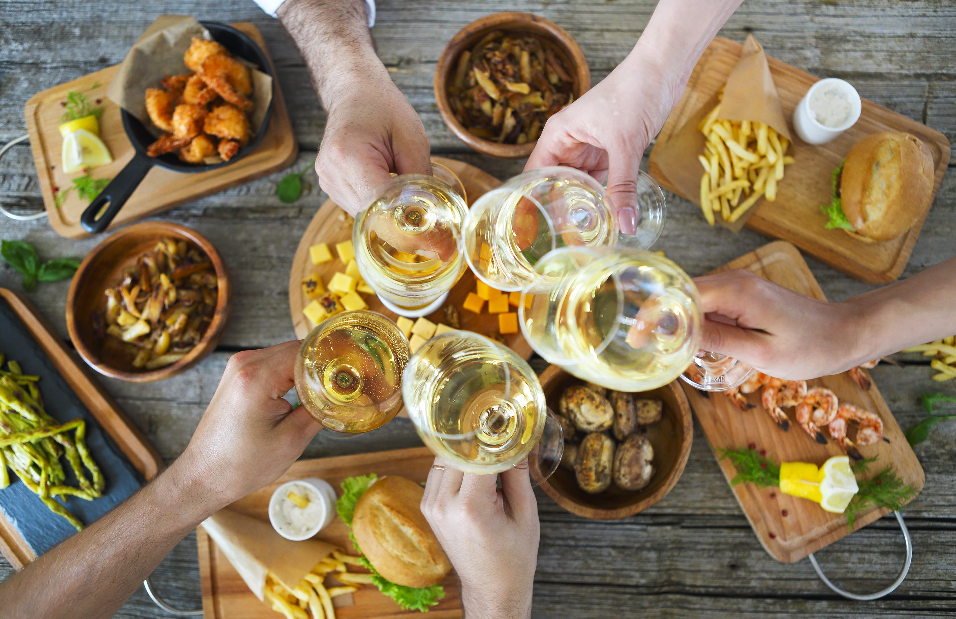 Hands,With,White,Wine,Toasting,Over,Served,Table,With,Food.