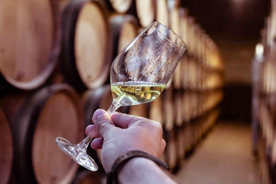 White wine on wooden oak barrels stacked in rows in order in cellar of winery.